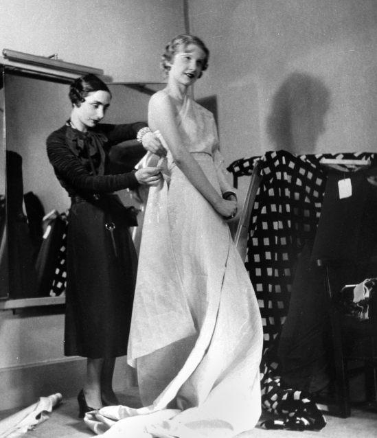 Germaine Krebs (1903-1993) dite Alix puis Madame Grès, à l'époque de la maison Alix Barton, créant un modèle drapé sur un mannequin. Paris, 1933.