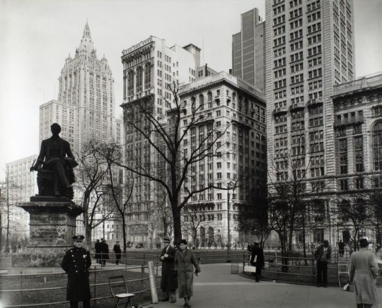 Berenice-Abbott-Changing-New-York-1935-1938-Madison-Square-looking-northeast-Manhattan-Policeman-stands-in-front-of-Seward-statue-shoe-shine-man-lounges-on-railing-right-Metropolitan-Life-building-rises-above-park-March