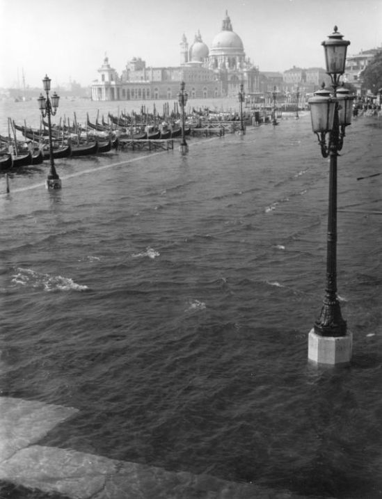 SANTA-MARIA-DELLA-SALUTE-AND-THE-DOGANA-DI-MARE-SEEN-FROM-THE-FLOODED-MOLO-DURING-ACQUA-ALTA-VENICE-1961-by-EDWIN-SMITH-C29569