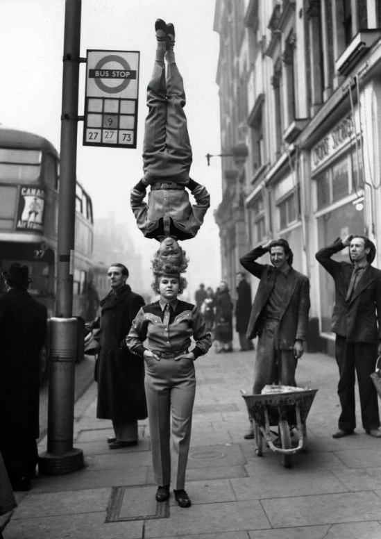 Two members of the Bertram Mills Circus walk head-to-head at Hammersmith Broadway in London, 1953