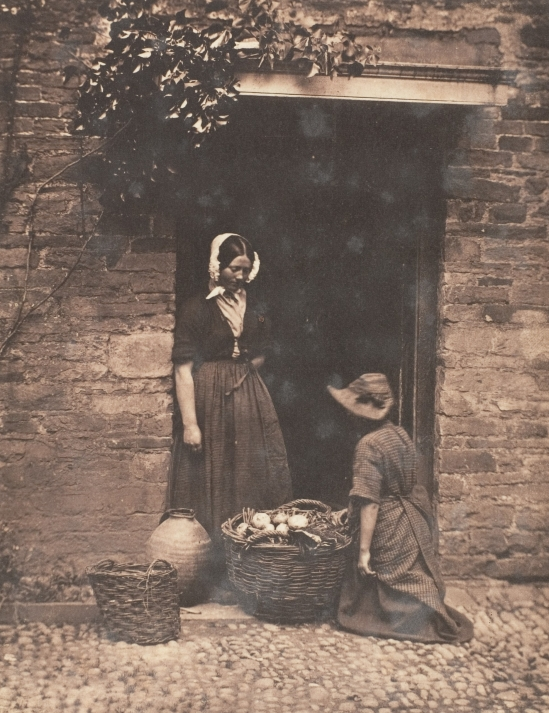 two_women_one_kneeling_and_one_standing_looking_into_basket_filled_with_vegetables-_met_dp143479.jpg